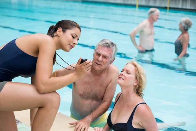 수영장에서 수석 수영에 시간을 보여주는 젊은 여성 트레이너