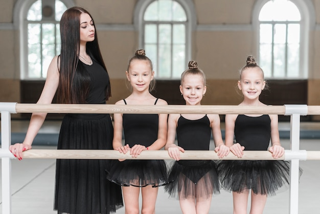 Young female trainer with her three ballerina girls standing behind the barre