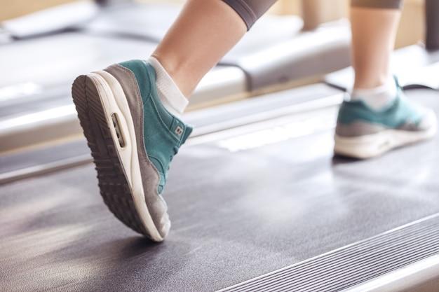 ジムの健康的なライフスタイルのトレッドミルで若い女性のトレーニング