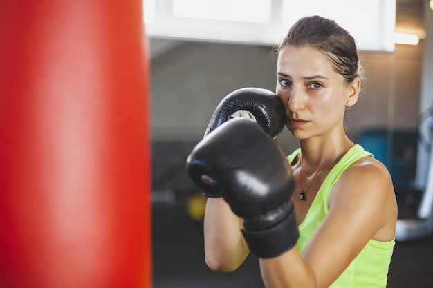 Le giovani donne si allenano in palestra e fanno esercizi di boxe con i guantoni da boxe davanti a un sacco da boxe