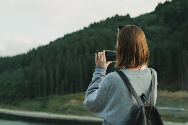 Young female traveler in grey sweatshirt taking photo on smartphone of mountain forest landscape