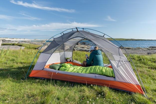 Молодая женщина-путешественница в лагере внутри палатки со своим мобильным телефоном