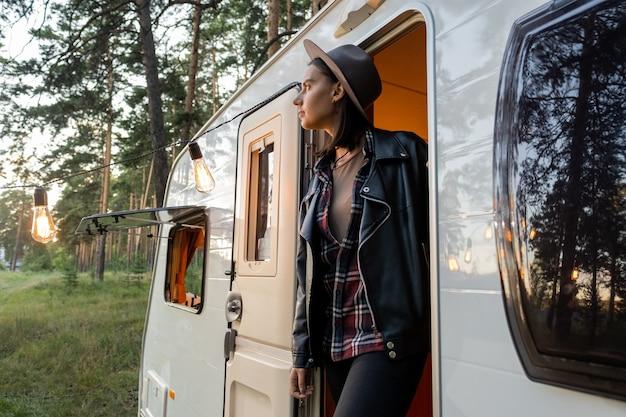 바퀴 달린 집에 모자와 검은 가죽 재킷을 입은 젊은 여성 여행자