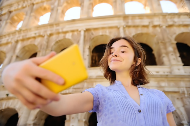 Young female traveler making selfie photo standing the colosseum in rome, italy