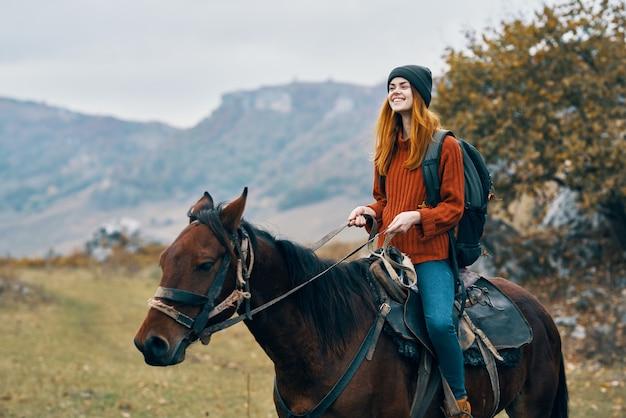 若い女性旅行者が馬と一緒に屋外でポーズ