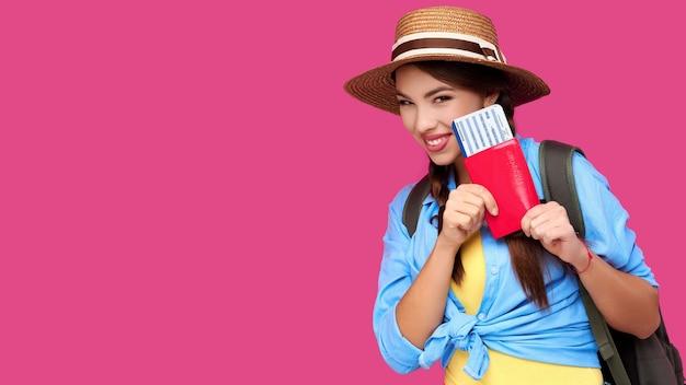 Молодая женщина-путешественница в повседневной одежде и соломенной шляпе с паспортом на розовом фоне изолировать. концепция туризма. студийный снимок