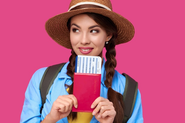 Young female traveler wearing casual clothes and straw hat holding passport with ticket on pink isolate background. tourism concept. studio shot