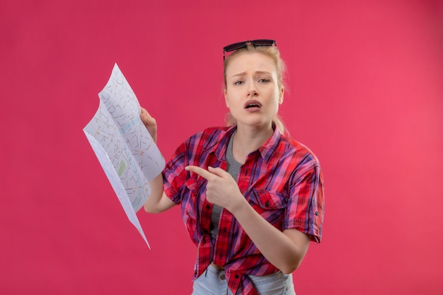 彼女の頭に赤いシャツと眼鏡を身に着けている若い女性旅行者は、孤立したピンクの壁に地図を描く