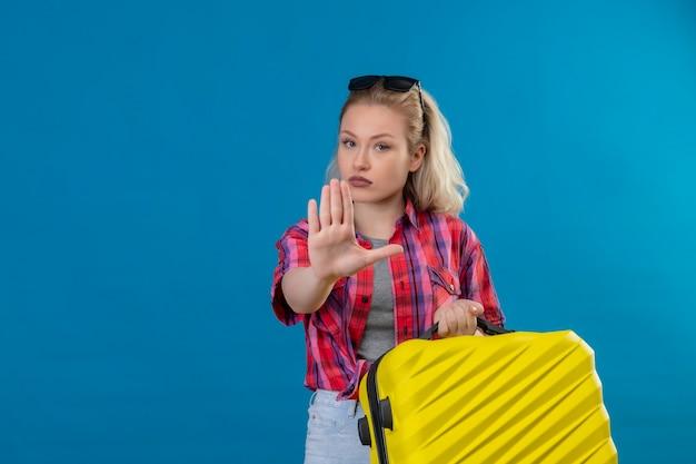 Giovane viaggiatore femminile che indossa la camicia rossa e gli occhiali sulla valigia della tenuta della testa che mostra il gesto di arresto sulla parete blu isolata