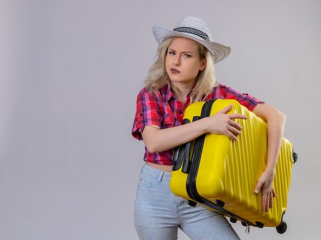 Giovane viaggiatore femminile che indossa la camicia rossa in cappello che tiene la valigia sulla parete bianca isolata