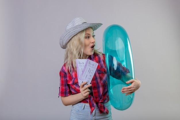 インフレータブルリングと孤立した白い壁のチケットを保持している帽子の赤いシャツを着ている若い女性旅行者