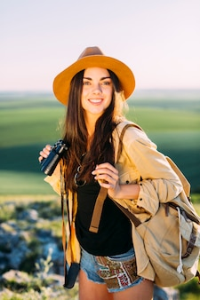Young female traveler with backpack and binoculars