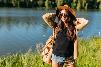Young female traveler with backpack, glasses and hat standing in front of lake