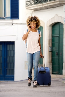 Young female traveling with suitcase and talking on mobile phone outdoors