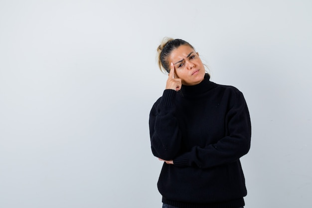 Young female in turtleneck sweater standing in thinking pose and looking pensive , front view.