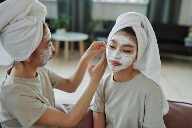 Молодые близнецы с глиняной маской для лица сидят на диване в домашней обстановке, пока одна из них помогает сестре надеть полотенце на голову