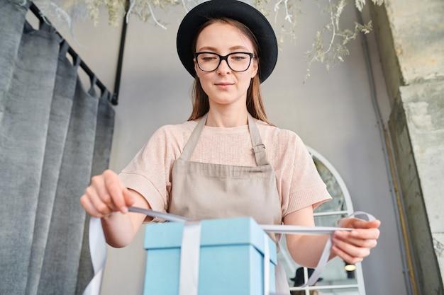 スタジオやショップでの作業中に青いギフトボックスの上にシルクリボンを結ぶ若い女性