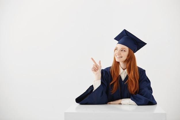Молодой женский выпускник университета в академической шапочка, сидя за столом, улыбаясь, указывая влево. будущий юрист или инженер, показывающий идею.