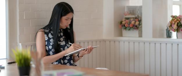 Молодая студентка пишет на цифровом планшете