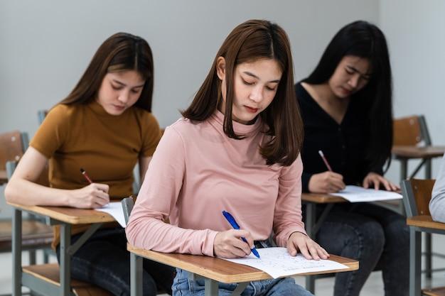 젊은 여대생들은 교실에서 시험에 집중한다. 여학생들은 교실에서 시험 연습을 진지하게 씁니다.