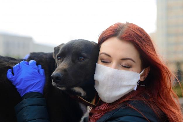 Молодая самка, используя маску в качестве профилактики распространения коронавируса, прогулки с собакой. глобальное изображение концепции пандемии covid-19.