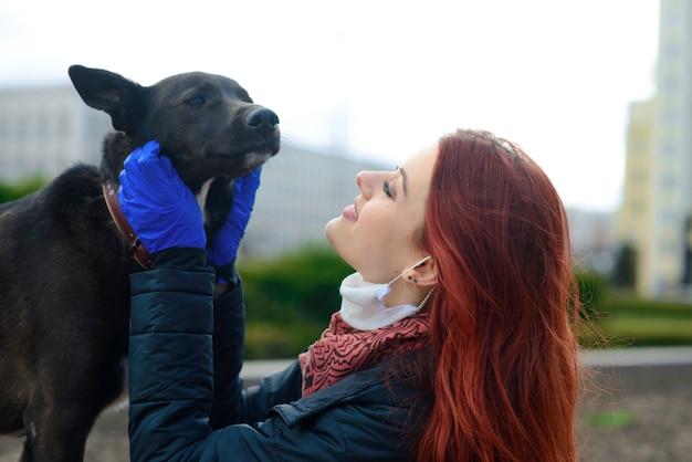 犬と一緒に歩くコロナウイルス拡散防止としてフェイスマスクを使用している若い女性。グローバルcovid-19パンデミックコンセプトイメージ。