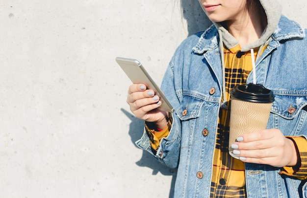 Young female using his smartphone on the street. woman texting on her phone