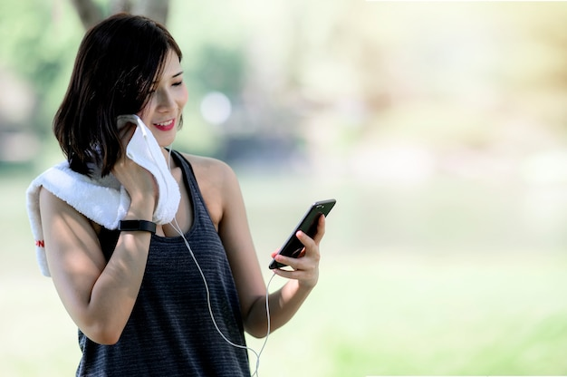 Young female using mobile phone after workout with happiness while standing outdoors.
