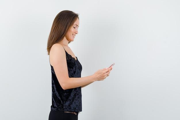 Молодая женщина с помощью мобильного телефона в черной майке, штанах и весело выглядит.