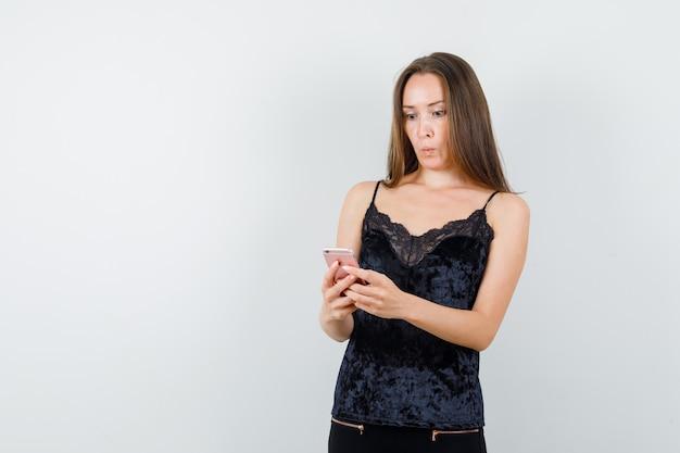 Молодая женщина с помощью мобильного телефона в черной майке, штанах и глядя задалась вопросом.
