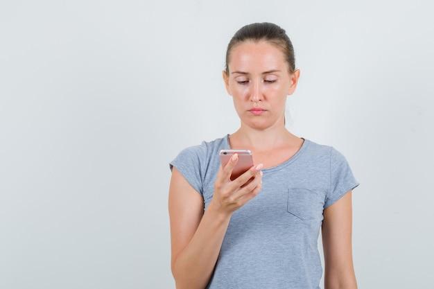灰色のtシャツを着て携帯電話を使用し、忙しい、正面図を探している若い女性。