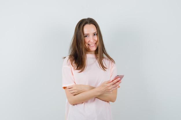 Молодая женщина с помощью мобильного телефона в розовой футболке и выглядит веселой. передний план.