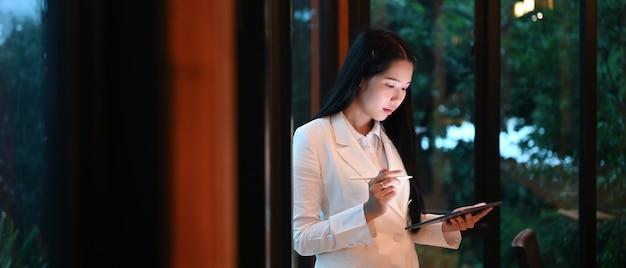 現代のオフィスのワークスペースでモックアップデジタルタブレットを使用して若い女性。