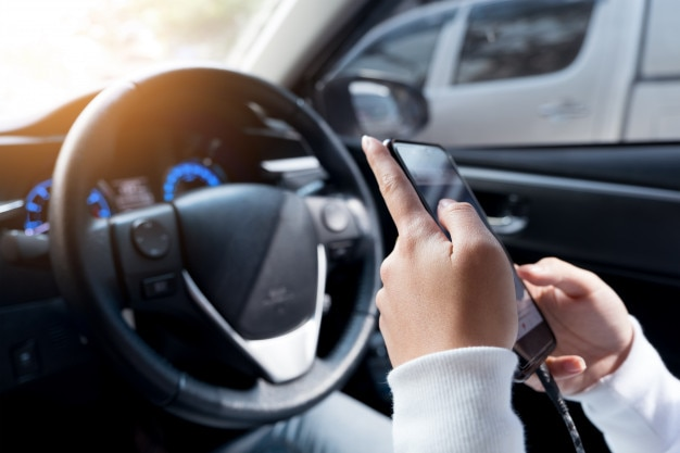 Young female using smart phone during driving a car