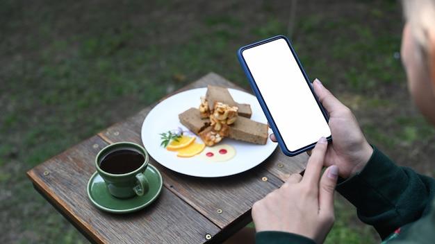 카페에서 쉬는 동안 커피와 케이크 사진을 찍는 스마트 폰을 사용하는 젊은 여성.