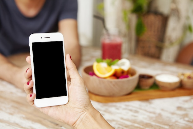 Young female using smart phone while having lunch at cafe. caucasian woman holding electronic device with blank screen with copy space for your promotional content.