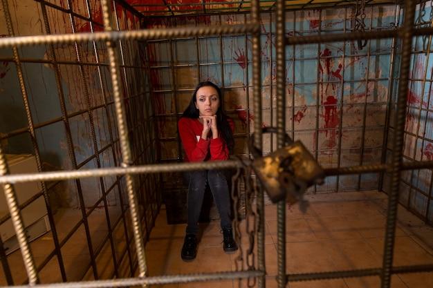 運命を待っている恐怖に座っている彼女の後ろに血が飛び散った壁のある金属製の檻に投獄された若い女性の犠牲者