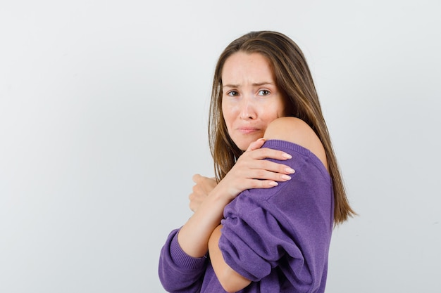 Young female in violet shirt hugging herself and looking offended .