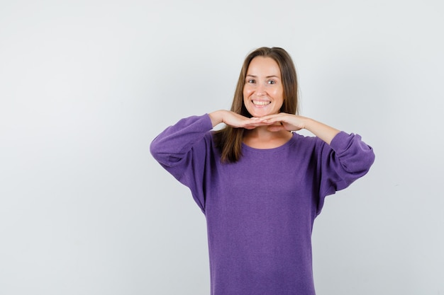 Young female in violet shirt showing oriental dance gesture and looking cheerful , front view.