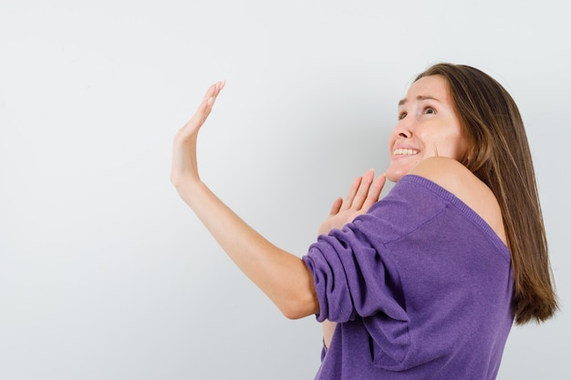Young female in violet shirt showing stop gesture and looking scared .
