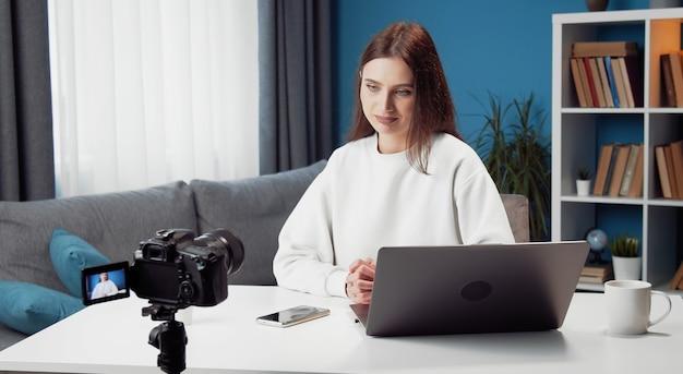 Молодая женщина-влогер записывает видео на камеру, сидя за столом перед ноутбуком дома