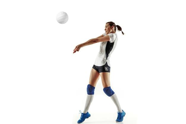 白い壁に隔離された若い女性バレーボール選手。スポーツ用品や靴、スニーカーのトレーニングや練習をしている女性。スポーツ、健康的なライフスタイル、動きと動きの概念。