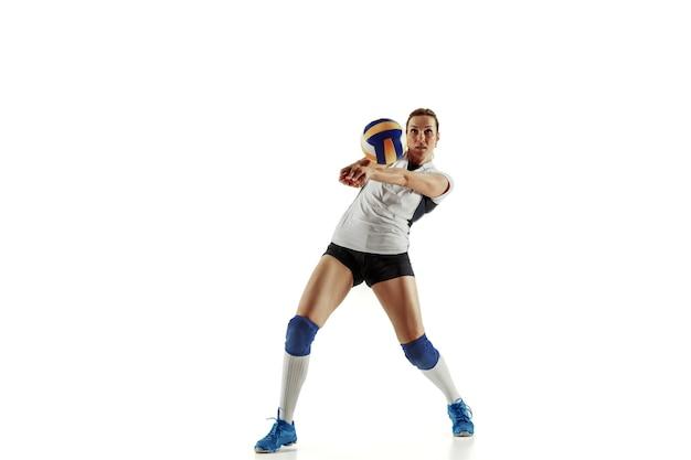 Giovane giocatore di pallavolo femminile isolato su sfondo bianco studio. donna in attrezzatura sportiva e scarpe o scarpe da ginnastica che si allena e si esercita. concetto di sport, stile di vita sano, movimento e movimento.