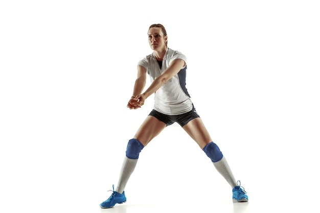 Young female volleyball player isolated on white studio background. woman in sport's equipment and shoes or sneakers training and practicing. concept of sport, healthy lifestyle, motion and movement.
