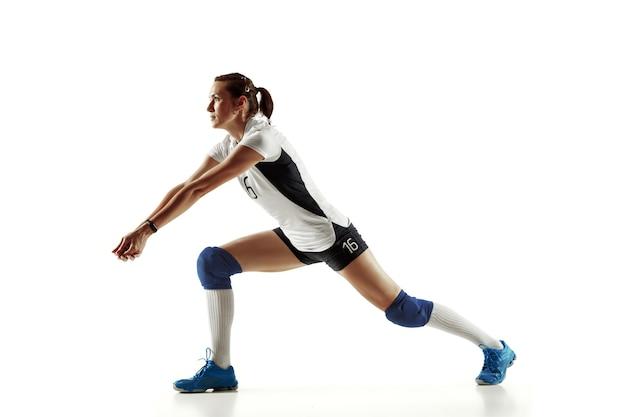 Giovane giocatore di pallavolo femminile isolato sul muro bianco. donna in attrezzatura sportiva e scarpe o scarpe da ginnastica che si allena e si pratica. concetto di sport, stile di vita sano, movimento e movimento.
