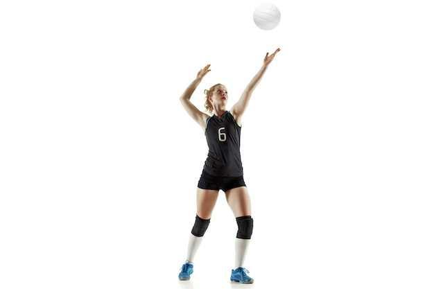 Young female volleyball player isolated on white wall. woman in sport's equipment and shoes or sneakers training and practicing. concept of sport, healthy lifestyle, motion and movement.