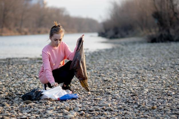 川沿いのゴミ収集若い女性ボランティア