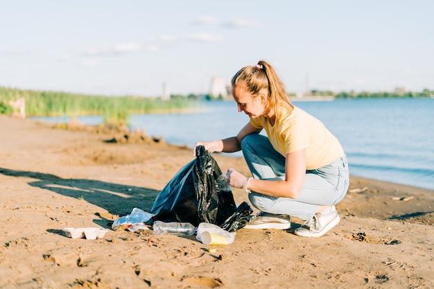 쓰레기를 줍고 플라스틱 병과 커피 컵을 청소하는 것에 만족한 젊은 여성 자원 봉사자