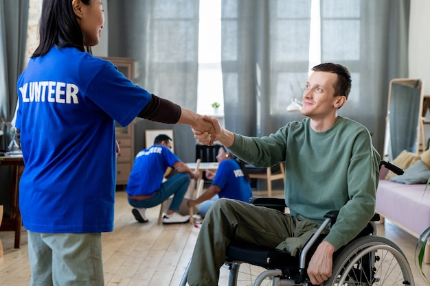 A young female volunteer shaking hands with a man in a wheelchair