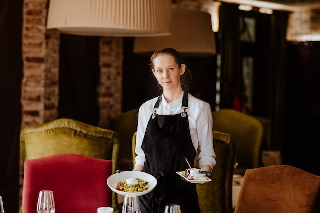 Молодая официантка в униформе с медицинскими перчатками, обслуживающая в ресторане